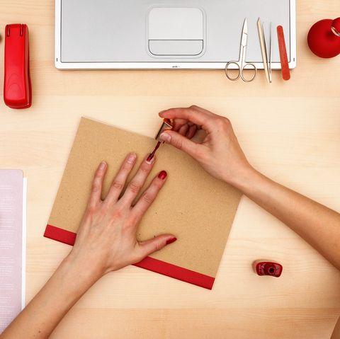 mujer pintandose las uñas de rojo manicura