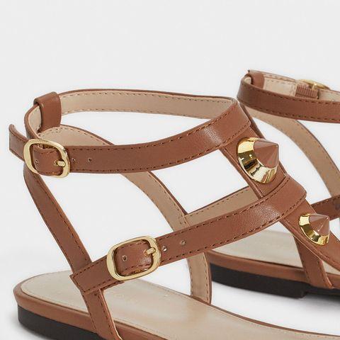 primer plano de unas sandalias marrones con tachuelas doradas