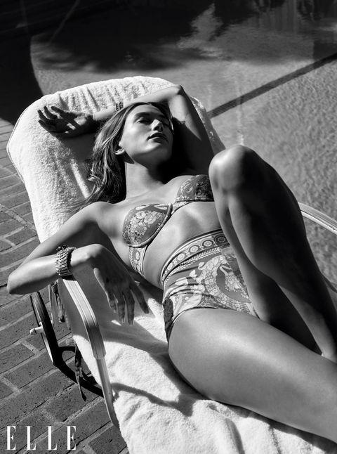 hailey bieber lies on a lounge chair alongside a pool