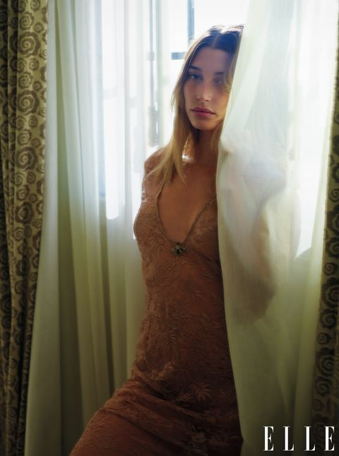 hailey baldwin stands among the draperies in a dress