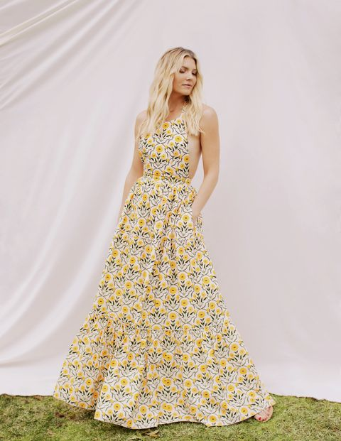 amanda kloots poses outside in a yellow, floral dress
