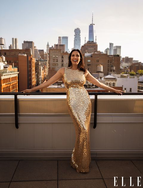 Padma Lakshmi standing on a balcony watching NYC, wearing a gold sequined gown