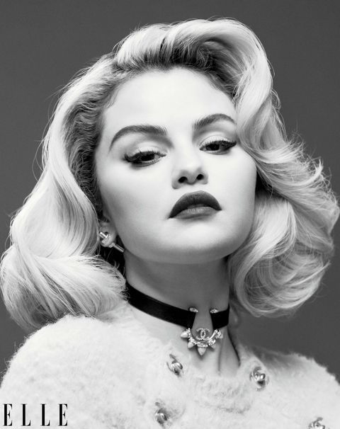 a black and white portrait of selena gomez shows her wearing a furry sweater and choker