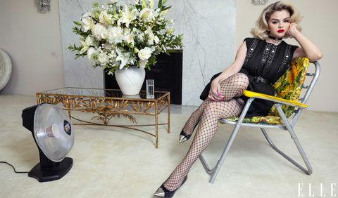 selena gomez sits on a folding chair in a black dress, a flower arrangement beside her