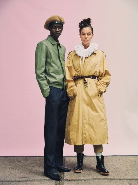 male models poses in green jacket with female model  in khaki trench