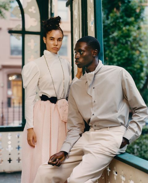 male and female model pose on porch in pastel and white clothes