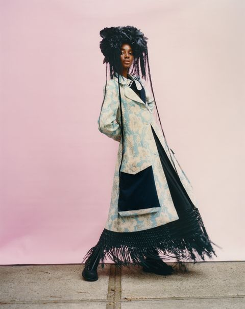 model in pale blue coat and black dress with black headdress