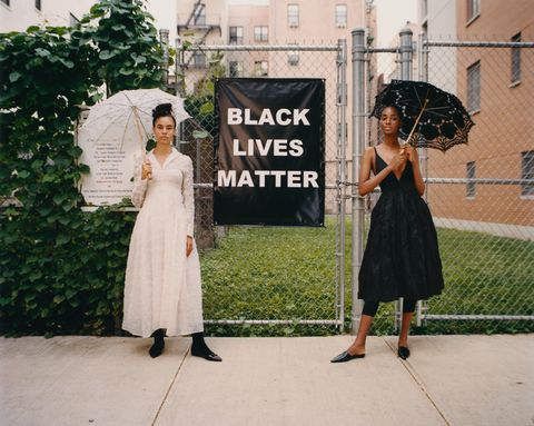 two models with parasols stand next to black lives matter sign in harlem
