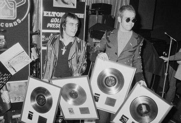Elton John (right) with his songwriting collaborator Bernie Taupin at a ceremony to award them gold discs for four of their co-written albums on April 26, 1973.