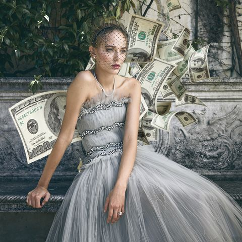 bride sitting on a stone bench in a garden in a dove grey dress and accessorized with diamond jewelry, designed with dollar bills scattered around her