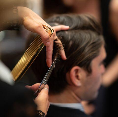 professional hair stylist cutting a man's hair at emerson joseph grooming lounge