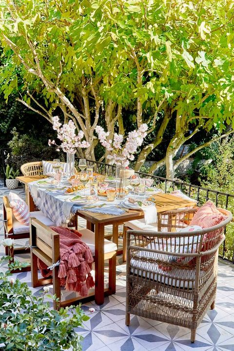 outdoor table with two vases on it with cherry blossoms