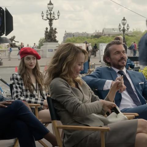 Эмили, Антуан и Сильви сидят на мосту во время фотосессии