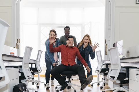 Employees pushing their boss on a swivel chair through the office