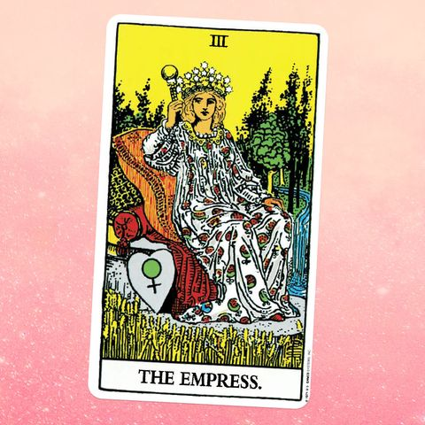 the tarot card the empress, showing a feminine person in a long patterned dress and crown, sitting on a throne in the middle of a field