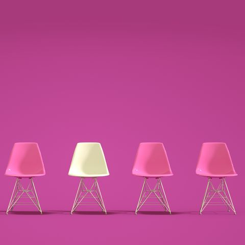 empty chairs against pink background
