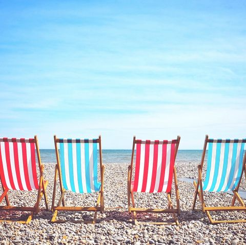 Empty Deck Chairs At Beach Against Sky