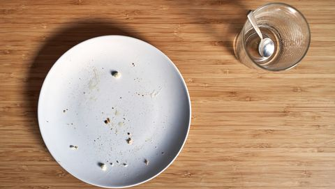 empty dish with bread crumbs and empty cup of coffee on a bamboo wooden table