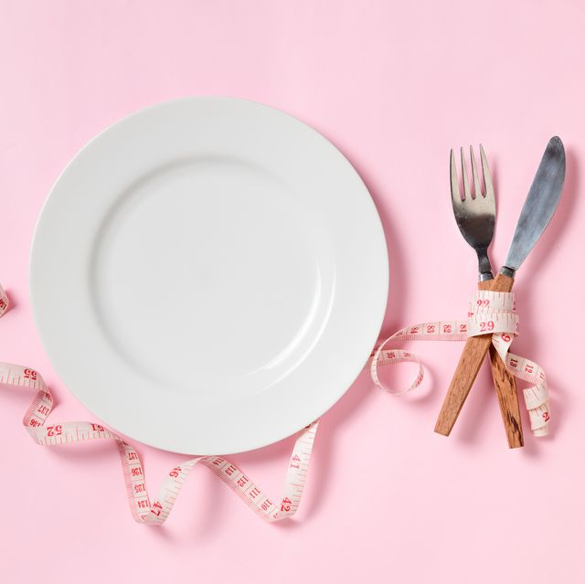 empty white plate with a knife and fork wrapped in measuring tape on pink background