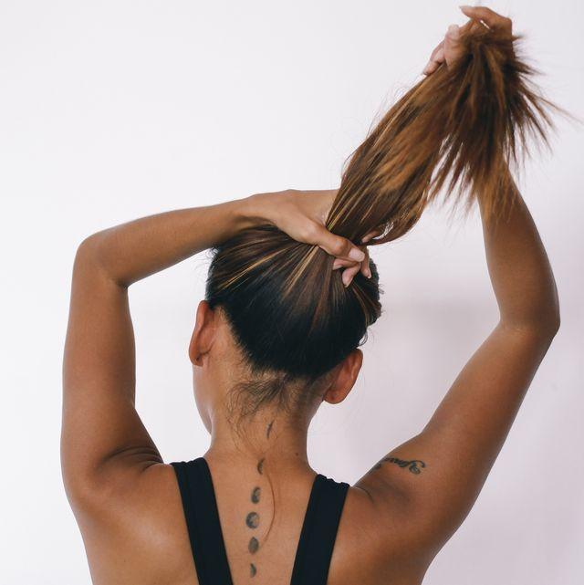 mujer de espaldas haciéndose una coleta