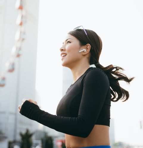 Energetic young sports woman listening music through in-ear headphones while jogging in urban city