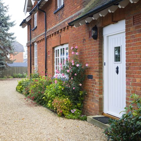 english country house and garden in autumn with a gravel driveway the house is victorian period, with flower borders filled with shrubs and perennials