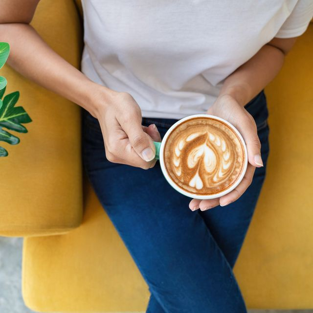 enjoying fresh coffee top view of beautiful young woman holding cup while relaxing on sofa at home