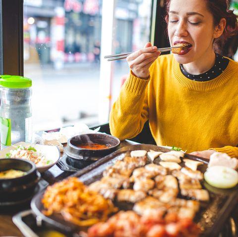 enjoying her travel in korean restaurant, tasting barbecue