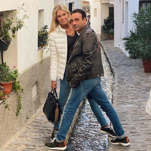 enrique ponce y ana soria posan juntos, con las mismas zapatillas, en una callejuela empedrada