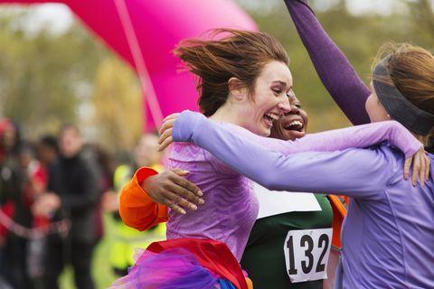 Enthusiastic female runners finishing charity run, celebrating
