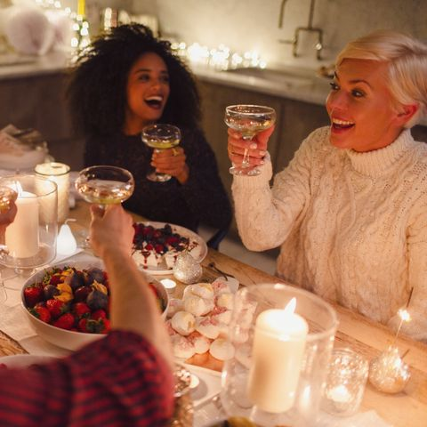Enthusiastic friends toasting champagne glasses at candlelight Christmas dinner