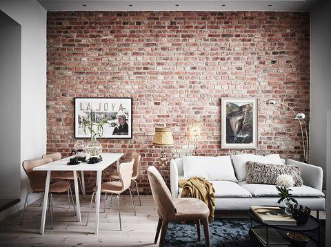 Salón y comedor con pared de ladrillo visto.Apartamento de estilo nórdico renovado