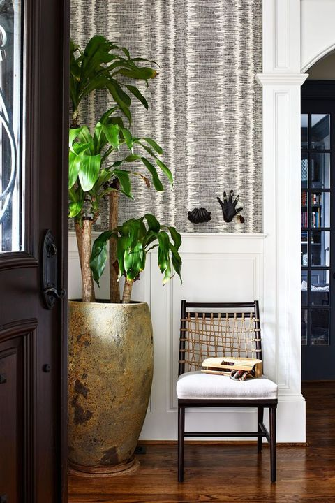 entryway with a chair and black hands on the wall that are key holders