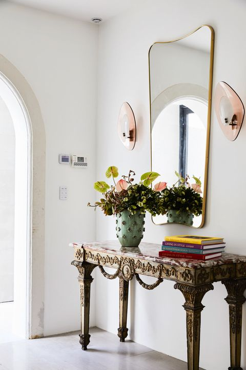 entryway with formal consol and modern mirror and sconces