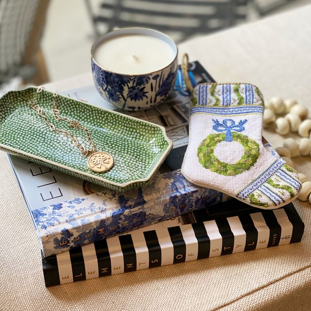green tray, candle, and festive stocking on top of two interior design books