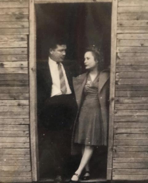 sepia toned photo of erin napier's grandparents standing in a wooden doorway