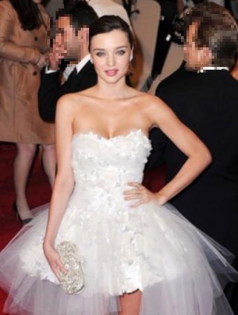 miranda kerr posando con un vestido blanco y la mano en la cintura