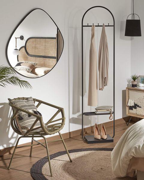 espejo con forma orgánica y marco negro en el dormitorio