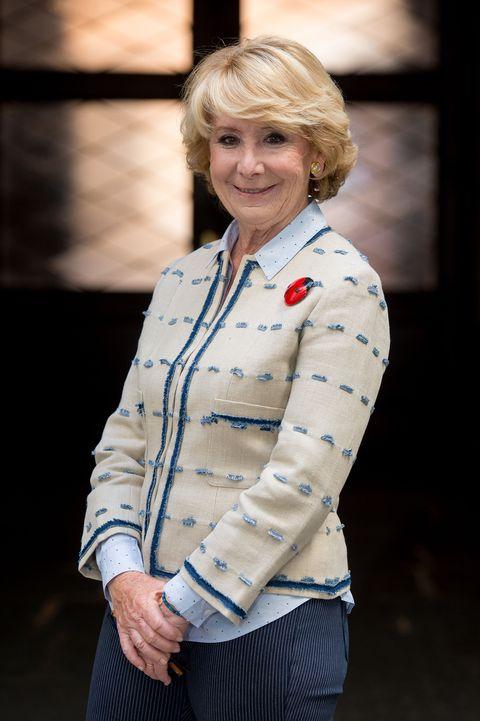 la política mira a cámara con una chaqueta beige y camisa azul claro en un plano medio