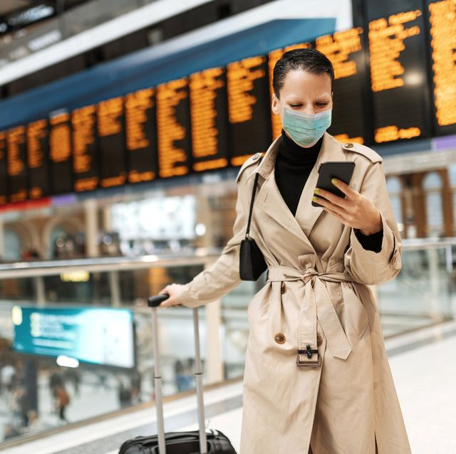 essential travels during lockdown   woman with face mask checking in online while waiting near arrival departure board