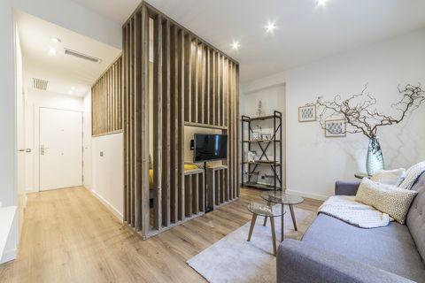 dormitorio integrado en el salón con pared de listones
