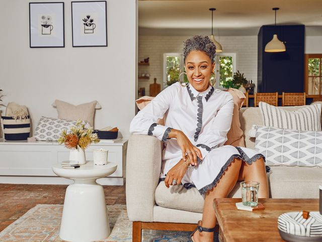 tia mowry sitting on a sofa in a room decorated with her etsy home decor collection