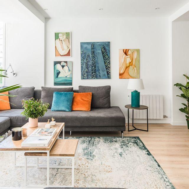 salón abierto con sofá en l gris con cojines de colores, paredes blancas decoradas con cuadros y una palmera