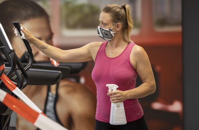 una mujer desinfecta una máquina de gimnasio antes de usarla