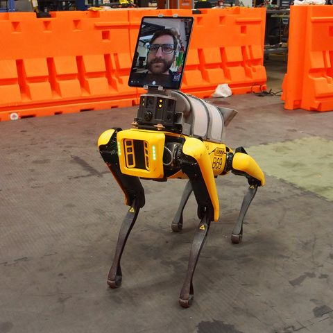 """a yellow robot dog, called spot, stands in the middle of a room in an industrial setting it has an ipad on its """"head"""" to show a person talking"""