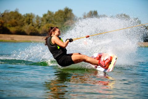 Young excited woman wakeboarding