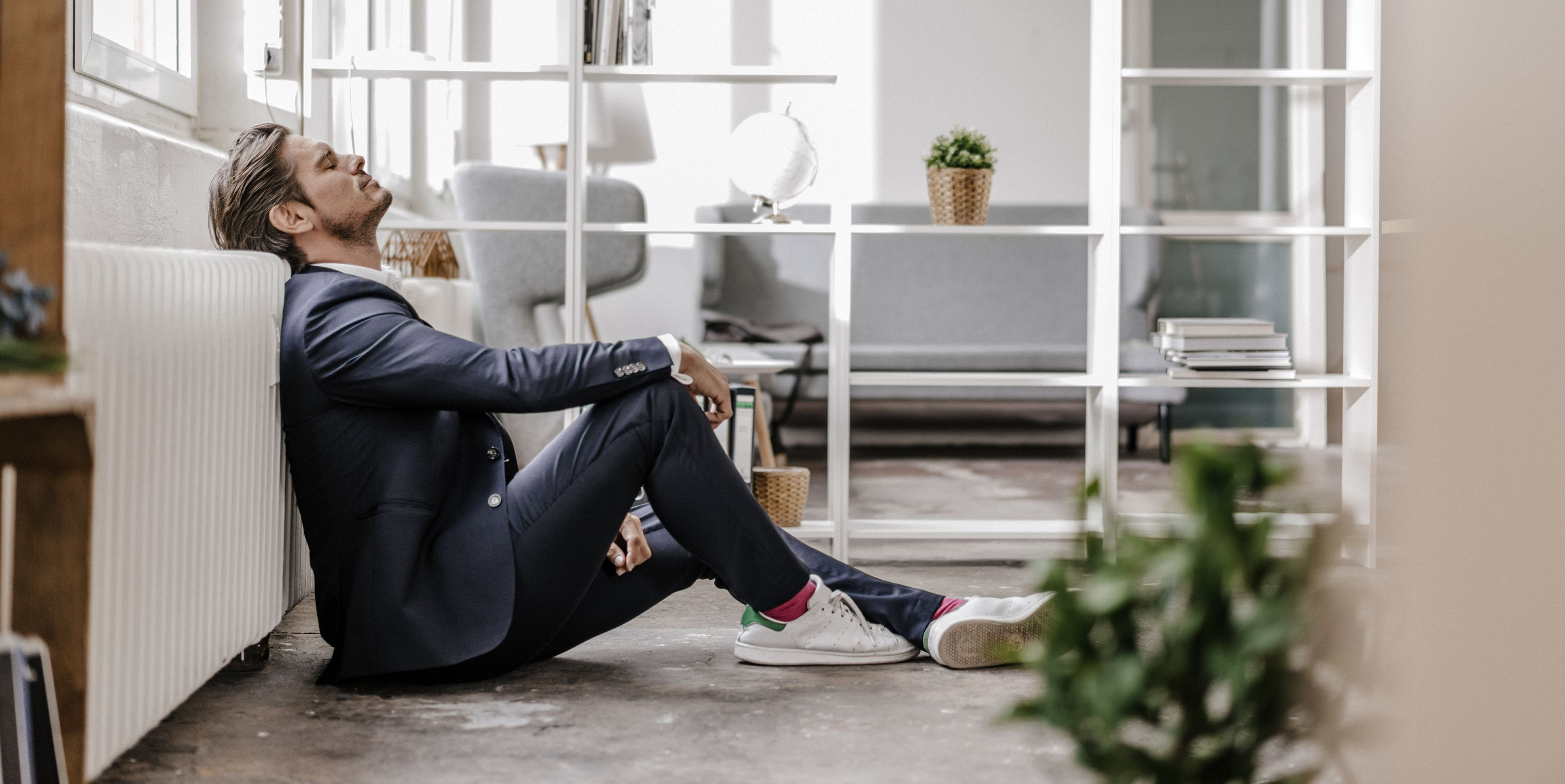 Exhausted businessman sitting on the floor