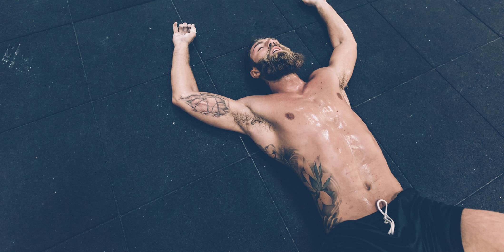 Exhausted male cross trainer lying on gym floor