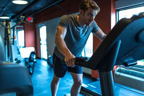 Exhausted mid adult man on gym treadmill