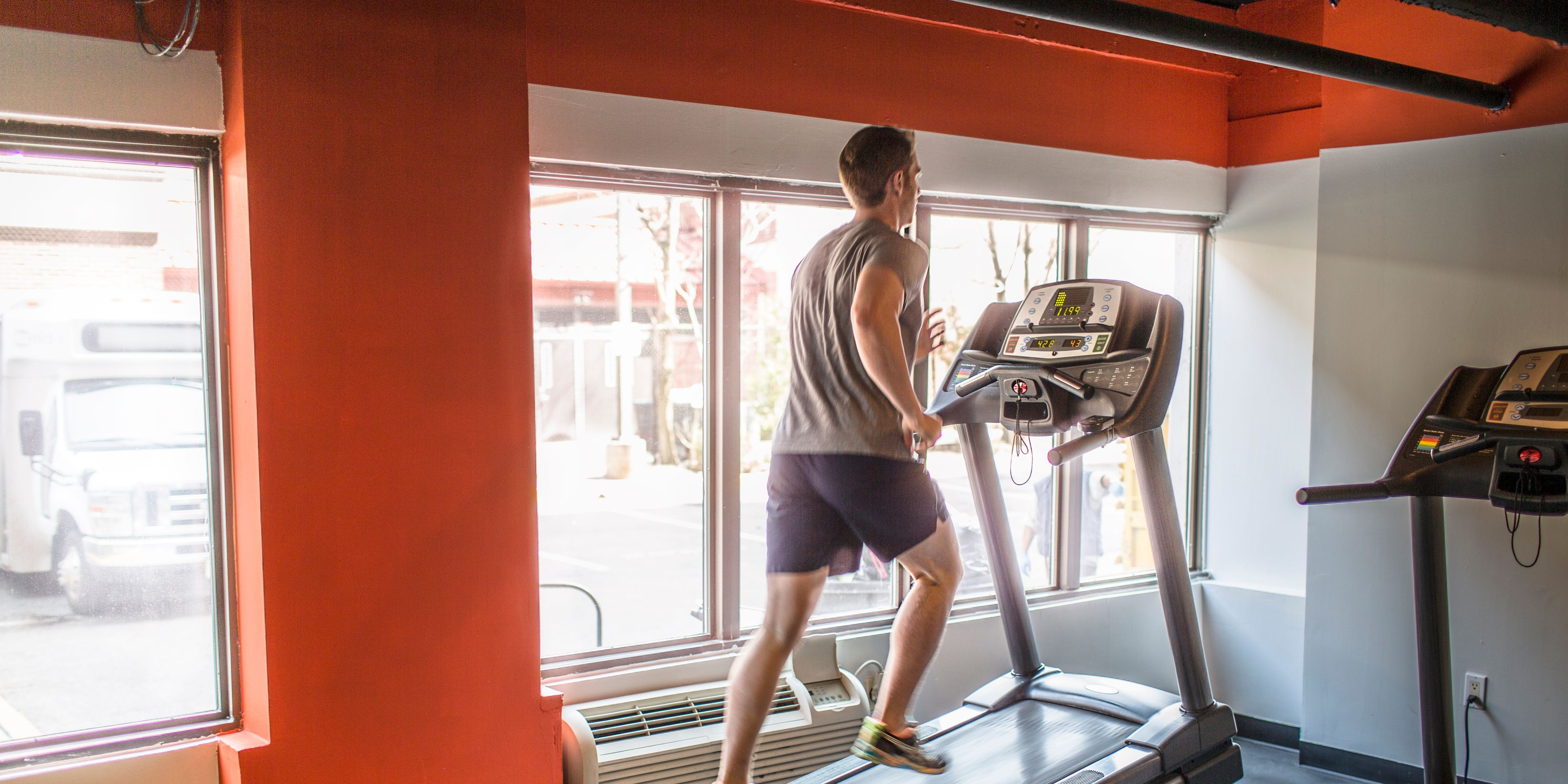 Exhausted mid adult man running uphill on gym treadmill